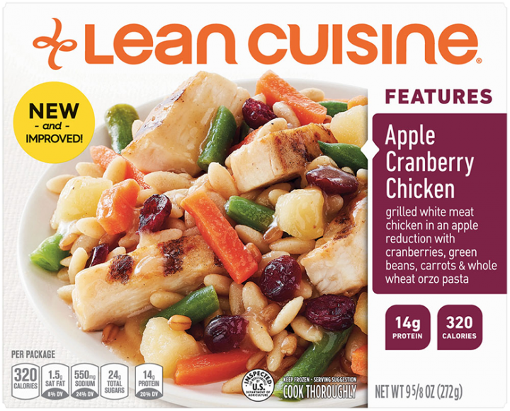 Front view photograph of a box of Apple Cranberry Chicken Frozen Meal featuring the orange Lean Cuisine logo and the features label beside the product name and chicken, cranberries, apples, vegetables and orzo in a white bowl on a white surface.
