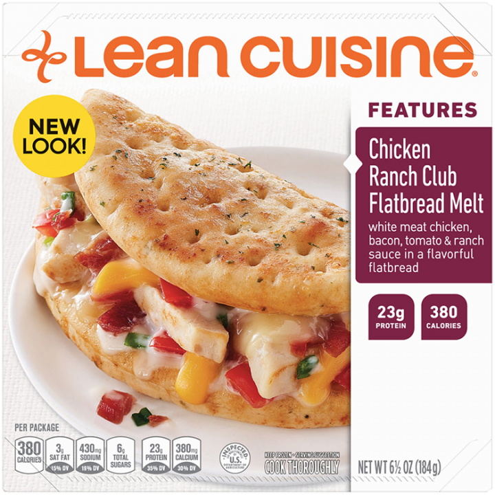 Front view photograph of a box of Chicken Ranch Club Flatbread Melt Frozen Meal featuring the orange Lean Cuisine logo and the features label beside the product name and a soft flatbread sandwich with chicken, bacon, tomatoes, a blend of creamy cheeses and ranch on a white plate on a white surface.