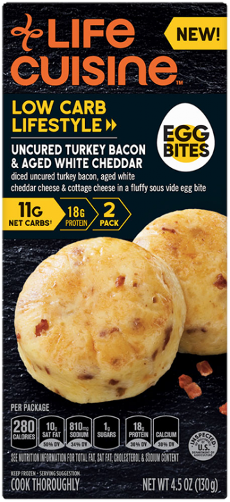 Front view photograph of a box of Uncured Turkey Bacon & Aged White Cheddar Egg Bites featuring the orange Life Cuisine logo and the Low Carb Lifestyle label beside the product name, an illustrated hard boiled egg with the words Egg Bites, and two actual egg bites with bits of bacon speckled inside it against a black textured surface.