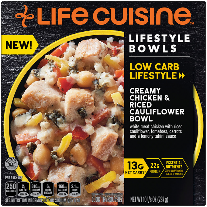 Front view photograph of a box of Creamy Chicken & Riced Cauliflower Bowl featuring the orange Life Cuisine logo and the Low Carb Lifestyle label beside the product name and a yellow bowl filled with chicken, riced cauliflower, tomatoes, and carrots against a black textured surface.