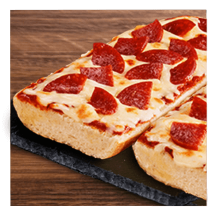 Pepperoni French bread pizza on a granite slate and wooden table top.