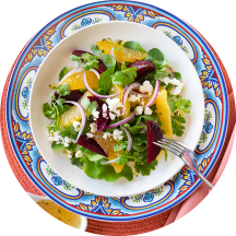 A plate of beet salad beside a fork, pink napkins, and a spoon of vinaigrette.