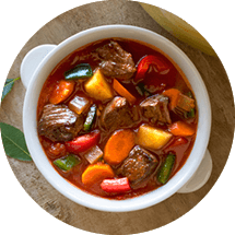 A white bowl of beef stew surrounded by bread, rice, bay leaves, a colorful pot and cloth napkin.