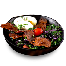A black bowl with fresh greens, a soft boiled egg and pieces of benevolent bacon.