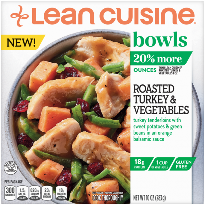 Front view photograph of a box of Roasted Turkey and Vegetables Bowl featuring the orange Lean Cuisine logo and the green bowls label beside the product name and roast turkey, sweet potatoes, cranberries, and greens tossed with gravy in a white bowl on a white surface.