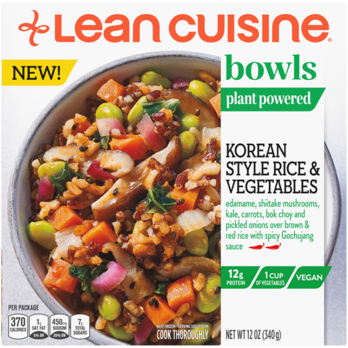 Front view photograph of a box of Korean Style Rice and Vegetables Frozen Meal featuring the orange Lean Cuisine logo and the green bowls label beside the product name and chicken, edamame, shiitake mushrooms, kale, carrots, bok choy & pickled onions over brown & red rice with spicy Gochujang sauce in a white bowl on a white surface.
