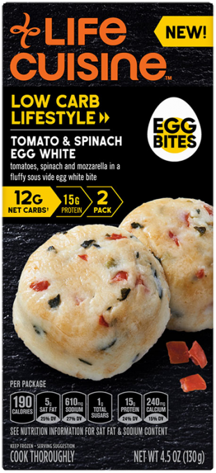 Front view photograph of a box of Tomato & Spinach Egg White Egg Bites featuring the orange Life Cuisine logo and the Low Carb Lifestyle label beside the product name, an illustrated hard boiled egg with the words Egg Bites, and two actual egg bites with bits of spinach and tomato speckled inside it against a black textured surface.