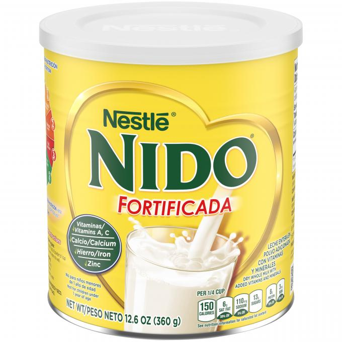 Front view of photograph of cylinder packaging for Nido Fortificada with a light yellow label, a white lid and gold heart above a photo of milk being poured into a glass.
