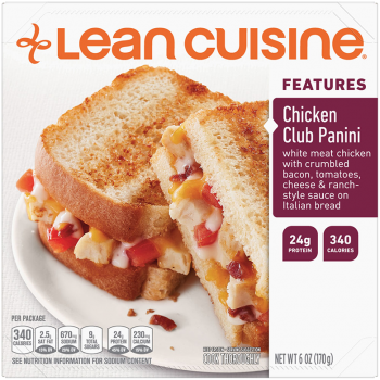 Front view photograph of a box of Chicken Club Panini Frozen Meal featuring the orange Lean Cuisine logo and the features label beside the product name and a crispy sourdough bread panini with chicken, crumbled bacon, tomatoes and a blend of creamy cheeses on a white plate on a white surface.