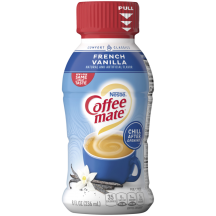 A blue bottle of Coffee mate French Vanilla Creamer with a red cap and blue label above a mug of coffee and vanilla beans.