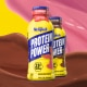 Waves of strawberry and chocolate milk behind bottles of strawberry and chocolate Protein Power.